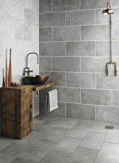 salle de bains moderne avec un carrelage mural et de sol en gris, table d'appoint et plan vasque en bois rustique et vasque en cuivre