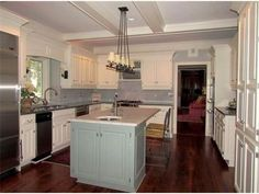 white cabinets grey island and chandelier