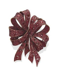 A RUBY 'BOW' DOUBLE CLIP BROOCH, BY MICHELE DELLA VALLE  Designed as a pavé-set ruby scrolling ribbon, mounted in titanium, (detaches to be worn as two brooches), in a Michele della Valle fitted black suede case