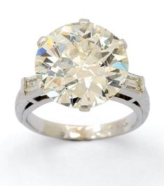 A Diamond and Platinum Ring, circa 1955  Set with an old European-cut diamond weighing 5.78 carats, flanked by a pair of baguette-cut diamonds, mounted in platinum