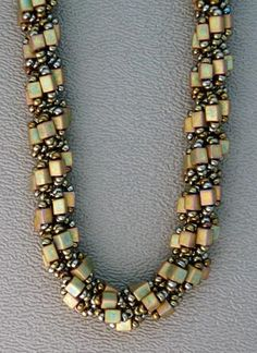 Spiral stitch tutorial  This necklace uses brown iris (metallic green) seed beads for the core and for the outside beads. There are 5 beads in the outside loops, and the center bead is a 3mm khaki metallic cube bead. Hex-cut, Size 8 Delicas also work well as a center accent bead.