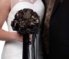 For a steampunk themed wedding, this striking bouquet is filled with satin flowers, metal gears, feathers, broach deco, sheer ribbon and decorative details. The gorgeous combination of black and antiq
