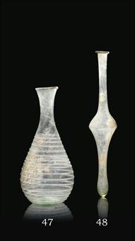 A ROMAN TRANSLUCENT PALE GREEN BLOWN GLASS FLASK 1ST-2ND CENTURY A.D.