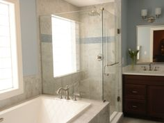 This shower went from all white to all wow! The shower walls are Midwest Tile Maxima Carnico Polished 12x12 in Lappato in a straight lay pattern. The accent tile is Sicis glass mosaic tile in Eucalyptus. Kohler Underscore bubble massage tub (relaxing!).