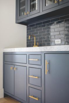 Dark blue cabinets adorning Lewis Dolan Bar Pulls and Knobs and a thick honed marble countertop holding a sleek brass faucet in front of blue glazed backsplesh tiles lining glass front upper cabinets in this stunning blue and white butler's pantry.