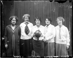ONE FIERCE BOWLING TEAM!  Five unidentifiedwomen, members of the Chicago Daily News bowling team, standing in front of a dark backdrop in a room. 1924