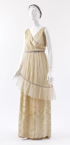 1913 Ensemble by Paul Poiret. Ivory silk damask, ivory silk net, and ivory China silk with rhinestone trim; ivory silk net with green and black silk gauze, applied tape and rhinestone trim; green and black silk gauze headdress with strands of rhinestones; ivory silk damask shoes. Via Metropolitan Museum of Art.