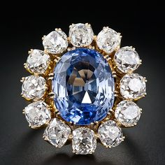 This fabulous, lavish and large scale (one-inch by 7/8 inch!) late-nineteenth century sapphire ring features a faceted oval 10.00 carat sapphire, of old Ceylon origin, with a bright and shining medium-light blue color. The sapphire is surrounded by twelve sparkling old mine cushion-cut diamonds, totaling five carats, set in classic Victorian coronet settings. While the top of the ring is one hundred percent original, the under gallery and ring shank were evidently replaced at a later date.