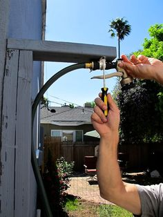 DIY outdoor shower using a simple hose, c clamps, and a wooden board.