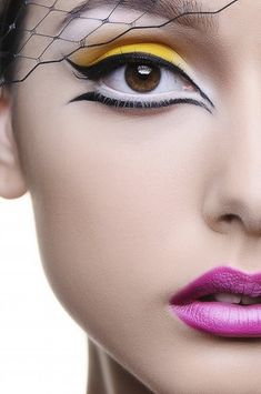 Yellow eyeshadow, bold black winged eyeliner with pinky/purple lip