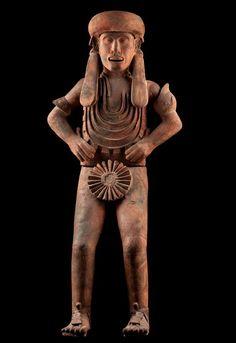 Huejotzingo,postclasico tardio,1325-1521 Escultura en la que vemos a un sacerdote dedicado al culto de la muerte. Lleva un tocado típico de algunas deidades relacionadas con el inframundo con largas orejeras que penden a los lados y caen hasta el pecho. Un collar con cuatro sartales le cubren prácticamente todo el pecho. Las manos descansan a ambos lados de la cintura y sobre el miembro tiene un rosetón de papel plegado propio de estas deidades.