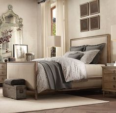 off white bedroom. herringbone wood floors. upholstered bed. gray bedding.