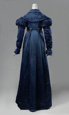 Wadded Coat (douillette). The Netherlands, c. 1820, silk, cotton (?), wood. In French douillette means soft, smooth, and comfortable. These wadded coats became fashionable in the Netherlands from the 1820s. This one has a matching ornamented belt at...