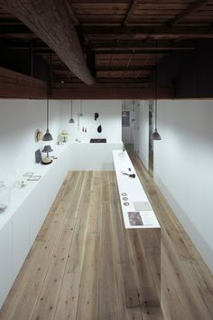 The single unit of an apartment building, built 40 years ago, was renovated as gallery and shop. The gallery shop sells jewelry, objects d'art, hat and photographs. All four sides of the center counter unit are covered with a mirrored surface, which reflects the floor planking, making the counter appear to be made of the same material. http://www.archdaily.com/490430/i-find-everything-makoto-yamaguchi-design/