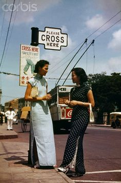 Women stand in front of a sign written in English, Malay, and Chinese. Singapore. 1941.