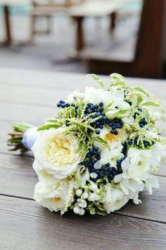 Wedding Bouquet Comprised Of: White Cabbage Roses, White Ranunculus, White Bouvardia, White Astilbe, Blue Privet Berries, Green Foliage