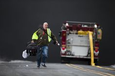 Week of Feb 21-27, 2015 A man carrying a baby runs from a wall of heavy, black smoke formed after a gasoline tanker, carrying about 9,000 gallons, overturned and exploded Monday on a highway in Pennsauken, N.J. Nearby homes were evacuated. MATT ROURKE/ASSOCIATED PRESS