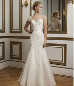 Shown in Alabaster/Nude Intricately beaded sleeves, V-neckline fit and flare gown rich in color and glamorous in every way. Inspired by a true work of art, a painting Available colors: Alabaster/Nude, Ivory, White