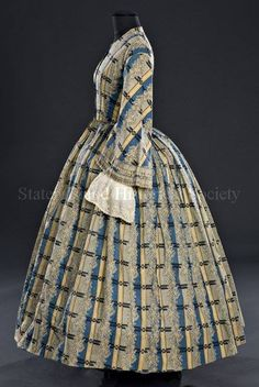 "Long pagoda sleeves are bias-cut and pieced; sleeve diameter is 12"" at bottom edge. Sleeves are trimmed with two rows of gray-blue gathered ribbon and lined with basted-in undersleeves. Gathered skirt is sewn into piped waist of bodice. Skirt has been shortened; the original hem, which is now turned under, is bound with wool braid and faced with brown polished cotton."