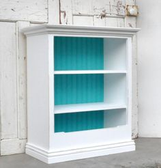 Add moulding to plain bookcase, paint, distress, add baskets (I like how the back of the bookcase is painted in a different color).