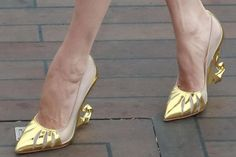 Angelina Jolie shows off her gold Christian Louboutin shoes at the Shanghai photocall for Maleficent. The actress has worn white and black versions of the same shoe at the London and Paris photocalls for the film.