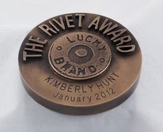"Lucky Brand engaged Bennett Awards to create custom awards for a new employee recognition program. These awards are called The Rivet Award. For these awards, Bennett Awards created a new custom design that supported the Lucky Brand brand image. The form-factor for this design is a unique, custom-designed medallion. As their centerpiece, these medallions feature a raised image of a rivet – like those found on Lucky Brand jeans, along with the award name: ""THE RIVET AWARD""."