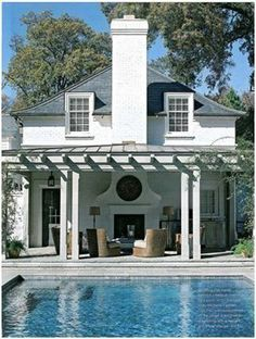 Classic white house with pergola covered patio by the pool.