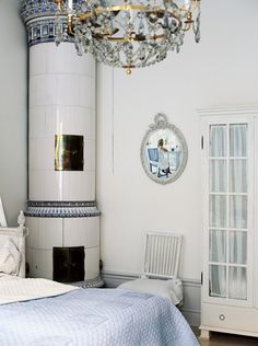 Gustavian bedroom with old Swedish tiled stove in white and blue.  Ledighetsparadiset Solåkra