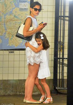 In for a tight hug: The white-bow wearing Suri Cruise hugged mom Katie Holmes tight as they stood outside the subway platform http://dailym.ai/1rb6taL