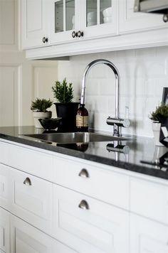Påkostat kök med enhetlig utformning till fastighetens karaktär - massiv granitskiva, vitrinskåp, spegelluckor och tidsenliga beslag. LUCKA: Meny vit | Ballingslöv