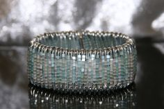 Safety Pin Cuff Bracelet with silver safety pins, light aqua, and white, glass tube beads. $18.00, via Etsy.