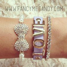 "Pearl bow bracelet, leather lavender gold ""love"" lettering bracelet, and rhinestone bracelet."