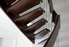 Bolzentreppe aus dunklem Holz wirken modern, kombiniert mit weißen Wänden