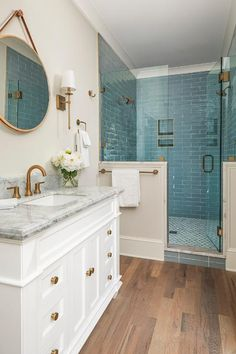 Sea blue shower walls create a spa like feel to a walk in shower featuring brass shower fixtures and a frameless glass door. Glass Tile Bathroom, Blue Glass Tile, Bathroom Renos, Small Bathroom, Glass Tiles, Teal Bathrooms, Frameless Glass Shower Doors, Bathroom Vanities, Master Bathroom