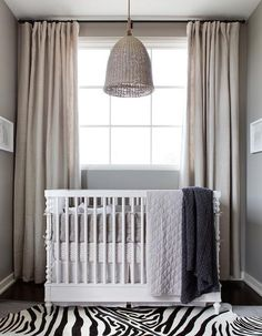 White and gray boy's nursery features a Restoration Hardware Baby & Child Seagrass market Pendant hanging over a Calais Spindle Crib dressed in Wa… - Parenting Grey Nursery Boy, Nursery Neutral, Safari Nursery, Grey Crib, Neutral Nurseries, White Nursery, Themed Nursery, Baby Boy Rooms, Baby Boy Nurseries
