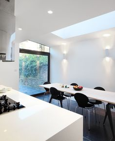Platform 5 Architects Same colour table top as the worktops. Dark chairs in white kitchen.