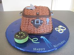 Fishing Creel - Fly fishing creel basket cake for my Dad on his 80th birthday. Pumpkin chocolate chip cake with chocolate buttercream basket weave and fondant decorations. Reel is small cake with fondant fishing line.