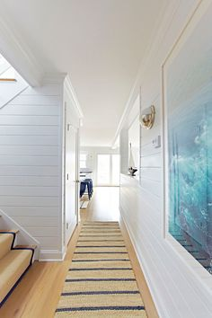 love white wood panel walls with the ocean photo on it and the rug to stop all the sand!