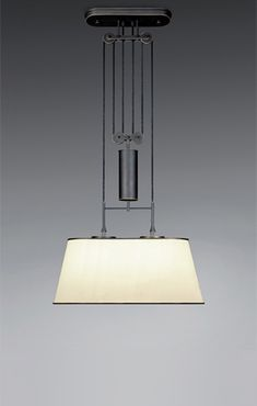 The Zylinderzug suspended luminaire boasts a large, oval silk shade. Its height adjusts via Kalmar Werkstätten's signature black cord running through four rollers suspended from a ceiling plate, with the counterweight located in the central cylinder. The mechanism, equally an aesthetic accomplishment, is finished in black bronze featuring highlighted edges.