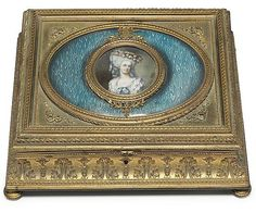 A FRENCH ORMOLU AND ENAMEL TABLE BOX <br />LATE 19TH CENTURY <br />The rectangular hinged lid centred with a portrait of a lady, signed <i>David</i>, against blue-ground enamel, over a spreading foliate-cast case with toupie feet<br />4 3/8 in. (11 cm.) high; 12 in. (30.5 cm.) wide; 10 in. (25.5 cm.) deep <br />