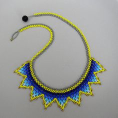 Color: blue, yellow, gray, bronze and black Size: 20 x 1.25 50 cm x 3.2 cm Beaded bead as closure For the small crown desing I decided to move away from the typical round choker. I was looking for a piece that can still give you the delicate handmade look, without be a staiment piece, something that you can use every day, so I created this simple shaped necklace where the coloors play a main part on every component (the chain, the center, even the beaded bead that is used as closure). You…