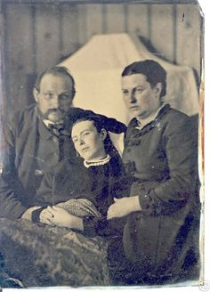 Victorian Post-Mortem Photograph.  The woman in the center has passed.  Post mortem photography was common when there wasn't a previous photo of the deceased.