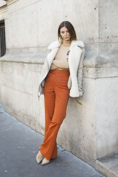This showgoer exhibits the outfit-transforming powers of wearing a jacket on the shoulders. Impractical? Maybe. Cool? Definitely. (Also, BRB—looking for our own pair of high-waisted, burnt orange trousers.)   - MarieClaire.com