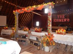 """This custom made archway and lighted """"Kisner"""" sign were both built by the groom! Decor for this September event was set with beautiful fall colors, wildflowers and sunflowers, and touches of western elements. The bride has a love of horses and the couple chose to include their interests on the shelves in front of their head table."""