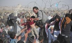 A  June 14, 2015 file photo of a Syrian refugee carrying a baby over the broken border fence into Turkey after breaking the border fence and crossing from Syria in Akcakale, Sanliurfa province, southeastern Turkey. The mass displacement of Syrians across the border into Turkey comes as Kurdish fighters and Islamic extremists clashed in