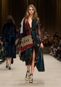 Check blanket poncho worn over a silk georgette dress with The Bloomsbury bag in dark bottle green leather and embroidery
