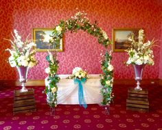 The Douglas Suite dressed for a wedding ceremony.  We dressed the registrars table with ivory organza and a teal bow.  Over the registrars table we dressed our bridal arch in an abundance of ivory flowers.  Either side of the bridal arch stood on crates were two silver urns filled with flowers to match the wedding theme. www.am-flowers.co.uk