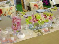 Green, White and Pink Cymbidium Orchids in rectangle clear glass. Cylinders submerged with Pink Cymbidiums. Sea Urchin candles and square votives with Pink Dyed water. Shell accents on table.