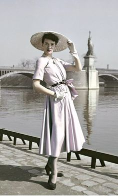 1948 Model in Dior's 'New Look' dress, in the background, the Pont de Grenelle bridge across the Seine River and a replica of the Statue of Liberty, photo by Robert Capa