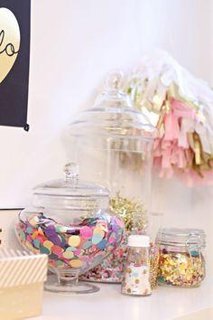 Coloque recipientes transparentes cheios de fofuras em pontos estratégicos, como o balcão, mesa de espera e prateleiras vazias! Enquanto mais simples for o conteúdo, mais interessante e criativo ficará o visual! Aposte em confetes coloridos, glitter, etc.